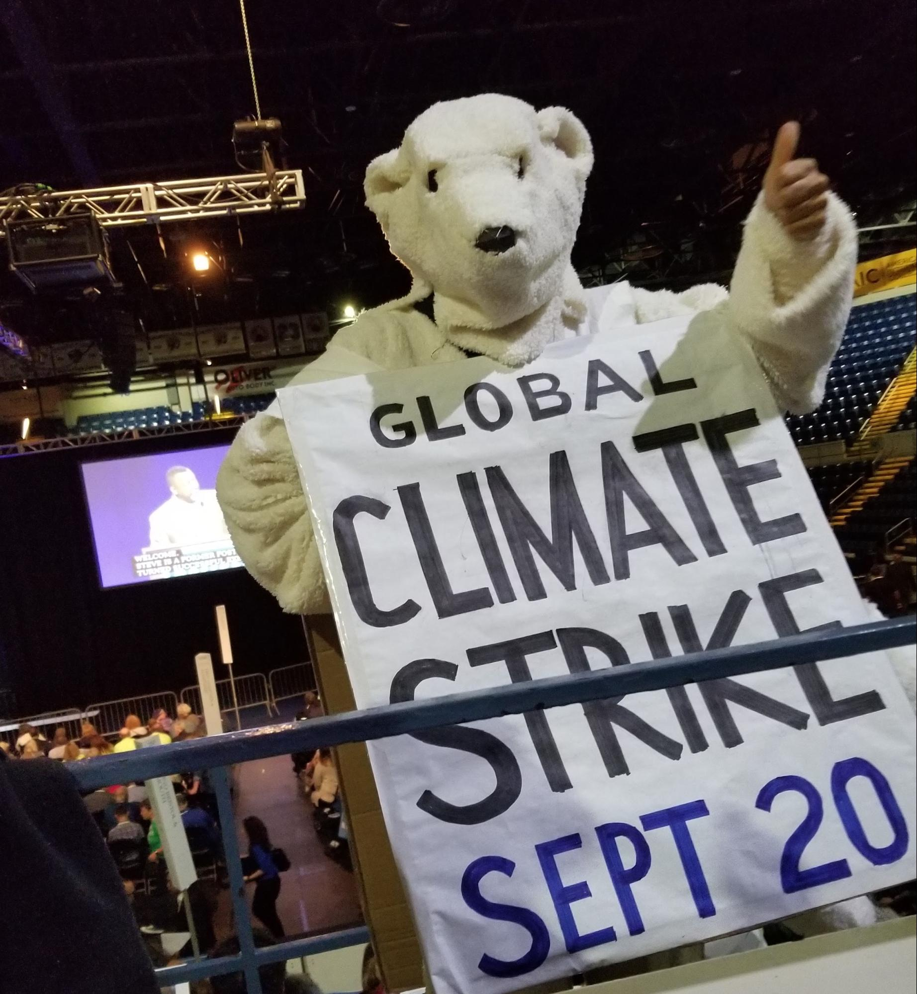 "Photo of protester in polar bear suit holding sign ""Global Climate Strike - Sept 2019"", promoting the Global Climate Strike at the Massachusetts Democratic Convention."
